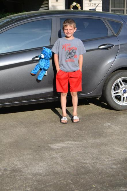 Luke McCarty standing next to the bear that hangs around on the door handle of the family car.